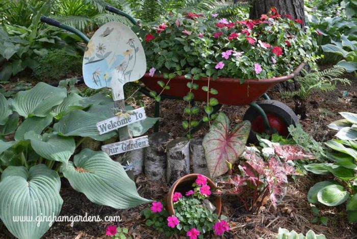Garden Vignette featuring a Vintage Wheelbarrow filled with flowers.