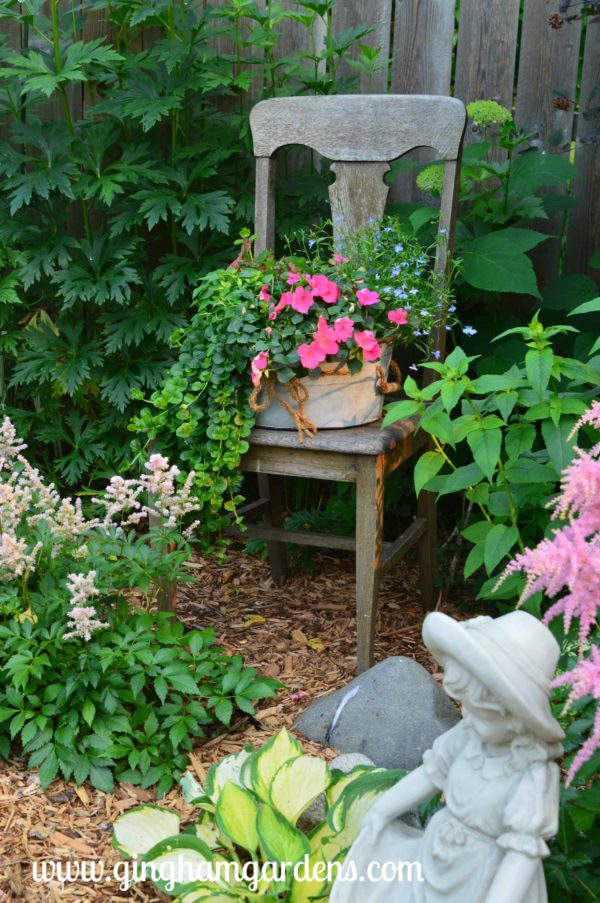 Old Chair in the Garden With A Galvanized Pot Full of Flowers