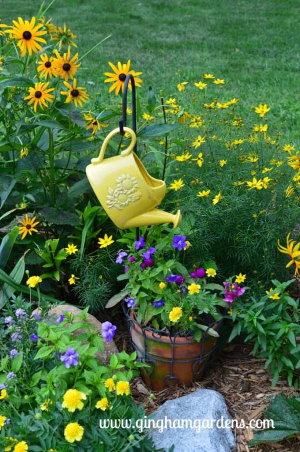 Decorative watering can hanging from shepherd's hook.