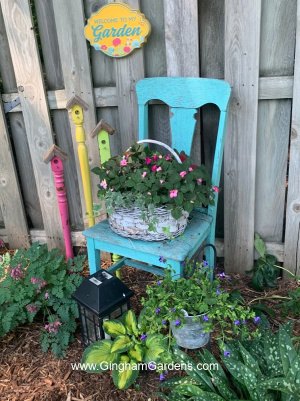 Image of an old chair, faux birdhouse stakes and a sign in a garden.