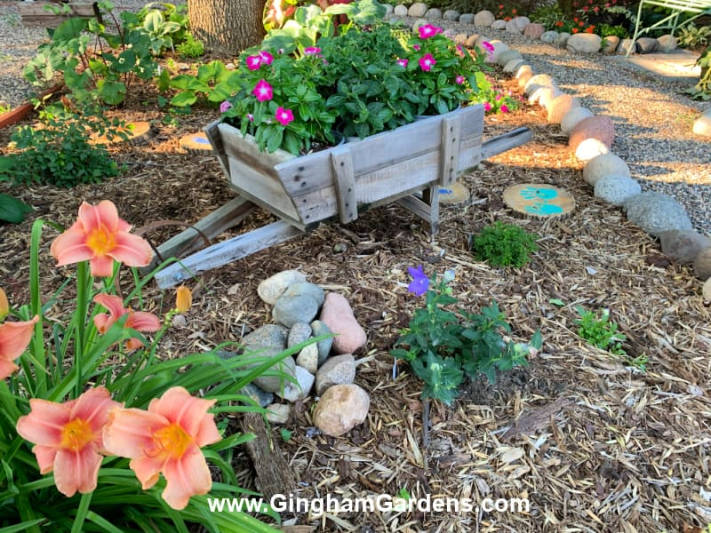 Image of a flower garden with an old barn wood cart