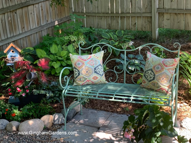Image of a bench in a shade garden