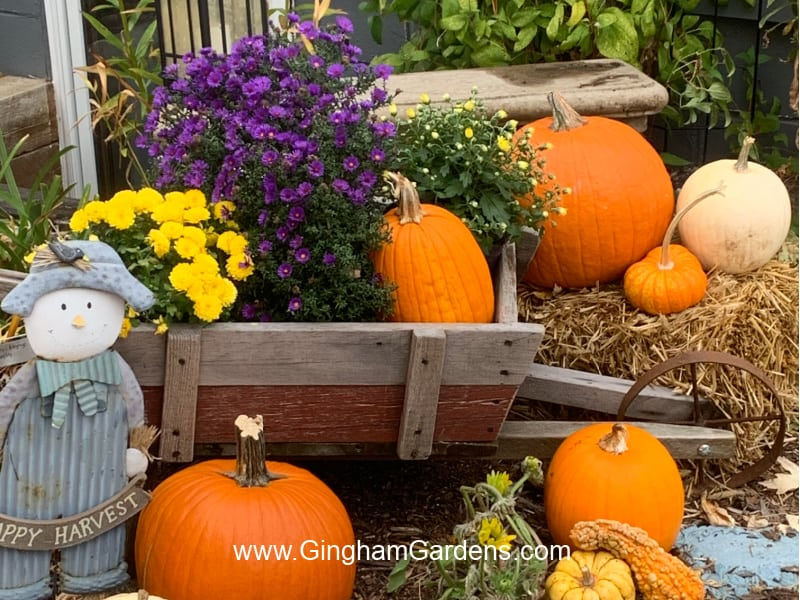 Image of a cart with fall flowers and pumpkins
